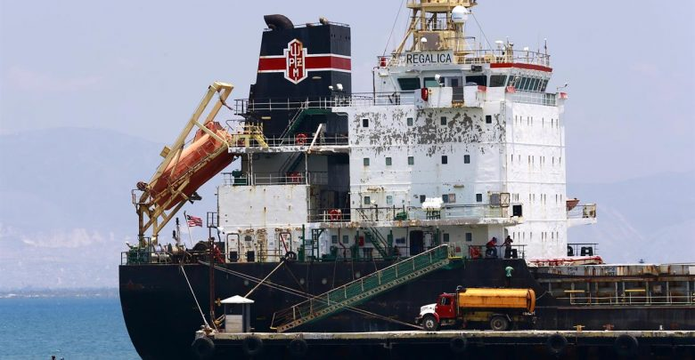 In this April 16 2019 photo a ship fills up on fuel from a tanker truck on the Thor terminal in Carrefour a district of Port au Prince Haiti.